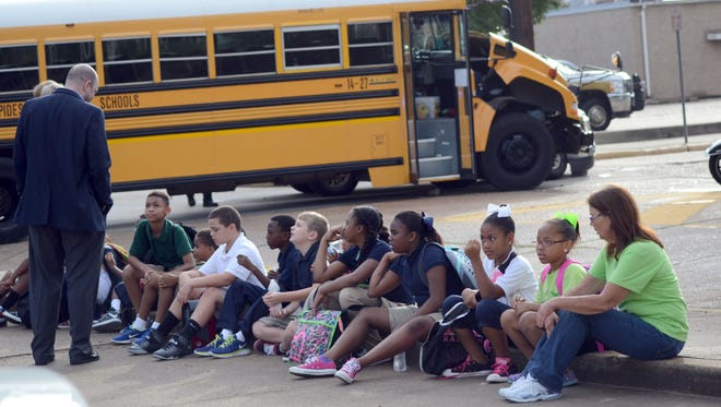 Peabody Montessori students wait in the parking lot on the corner of Foisy and Jackson streets in Alexandria on Friday after an accident with their bus and an SUV delayed their ride to school.