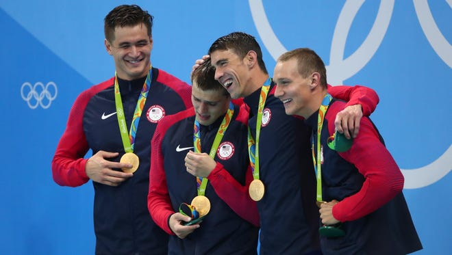 Nathan Adrian (USA) , Ryan Held (USA) , Michael Phelps (USA), and Caeleb Dressel (USA) celebrate with their gold medals after the men's 4x100m freestyle relay final in the Rio 2016 Summer Olympic Games.