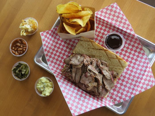 A grass-fed tri-tip sandwich with samples of side dishes is seen at J Wolf Catering in Ventura.