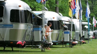 """6/1/07 6:17:52 PM -- East Wakefield, NH, U.S.A Airstream Rally Betty Girouard of Winchendon, MA and Elaine Duesel of Marlborough, MA (in white shirt) walk around amidst the Airstream travel trailers parked in the campground at the Lake Forest Resort in East Wakefield, NH.   They are members of the New England Unit of the Wally Byam Caravan Club International who gathered there for a rally.   Rallies have themes and this theme was """"Wedding Bells Rally"""" to host and celebrate the wedding of two of the club's members, Rick Cipot and Sandi Gould of Bethel, CT. Photo by Eileen Blass, USA TODAY Staff  ORG XMIT: EB 31963 Airstreams 6/1/2007  (Via MerlinFTP Drop)"""