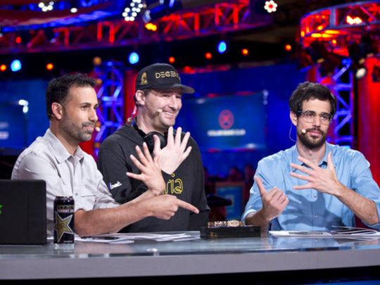 Phil Hellmuth, center, celebrates his 15th bracelet with broadcasters Ali Nejad, left, and Nick Schulman.