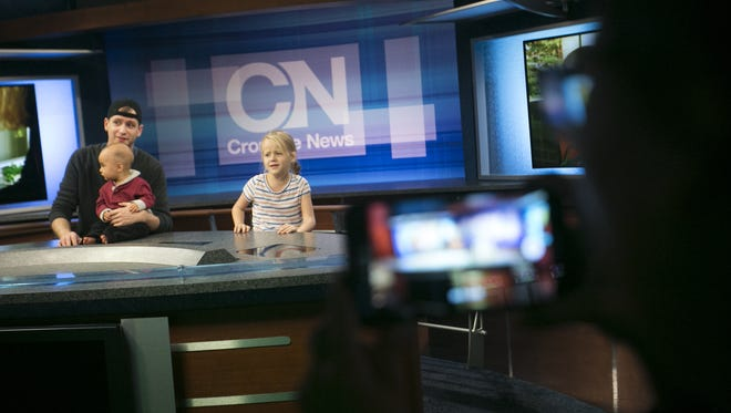 Katie Morin (right) takes a photo of Zach Hoffman holding his 8-month-old son, Maximilano, next to his 6-year-old daughter, Reesa, as they pose for a camera at the Walter Cronkite School of Journalism and Mass Communication at Arizona State University for the Arizona PBS KIDS Festival in Phoenix on Jan 16, 2017. PBS put on the festival to celebrate the launch of its new children's channel.