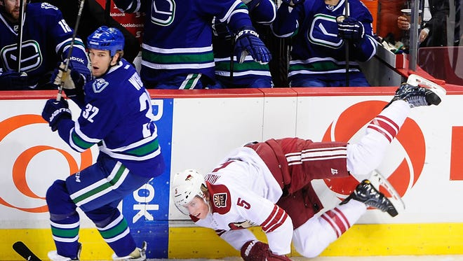 Phoenix Coyotes defenseman Connor Murphy (5) is checked by Vancouver Canucks forward Dale Weise (32) during the first period at Rogers Arena.