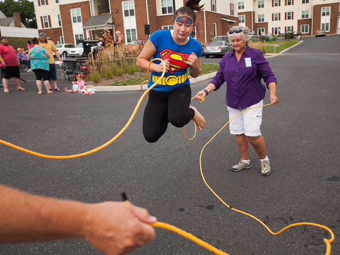 Amber Shea, 16, a resident of Montague Terrace Apartments, leaps between jump ropes spun by Kathy Doyle during an event to celebrate the start of new community services being offered at the housing development by a group of area churches called The Connection on Saturday, Aug. 2, 2014 in Stuarts Draft.