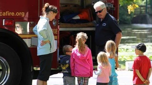 Ernie Williams, showing off one of IFD's trucks to some children