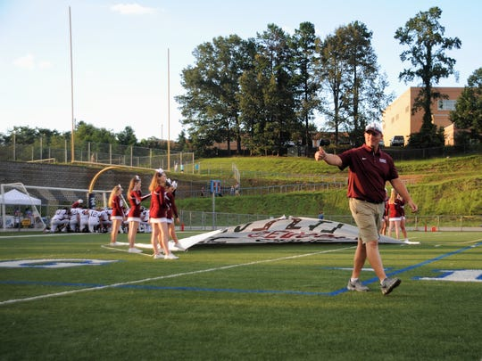 Owen Warhorses head coach Nathan Padgett takes the field for his team's season opener on Aug. 18 against Enka.