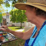 """Helen Jones of Melbourne Beach works on a oil painting of the old Mel-High building in downtown Melbourne Thursday afternoon. Helen was part of a """"Paint Out"""" protest of a possible sale of the old Mel-High  to a developer."""
