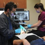 Dr. Bryan Mick examines patient Victor Cook recently as dental assistant Olivia Beach records the findings of the exam at Partnership Community Dental Clinic, which opened May 4 in Oshkosh. The clinic aims to serve low-income individuals and families who qualify for BadgerCare or are uninsured.