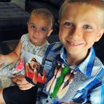 Christian McPhilamy, 8, of Melbourne shows photos of his hair he just cut off to donate to Children With Hair Loss. He gave up four ponytails -- three were 11 inches and one 12 inches. He started growing his hair December 2012 enduring criticism. Looking on is his sister Avalynn Norris age 3.