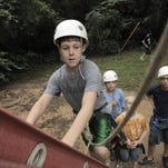 Jacob Kennedy climbs a ladder to get to the starting point for the zip line on the ropes course as his cohorts wait in line for their turn at the YMCA Camp Forbing in a Times file photo. The facility soon will be a memory as the property is developed.