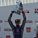 Justin Wilson hoists his second-place trophy Aug. 2 at the Honda Indy 200 at Mid-Ohio.