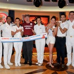 Senior management of the Carnival Sunshine celebrate Carnival fan Dennis Coleman's 1,000th day on a Carnival ship.