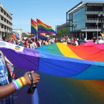 Participants in the Michigan Pride Parade march to the Capitol with a giant rainbow flag last August. The writer responds to last month's Greater Lansing Outlook package on extending Michigan's Elliott-Larsen Civil Rights Act to protect LGBT people.