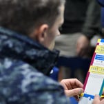 Fire Controlman 2nd Class Karl Weber, from Rome, Ga., reads a pamphlet about how to save for retirement during a Military Saves Campaign open house on the mess decks of the Ticonderoga-class guided-missile cruiser USS Cowpens (CG 63).