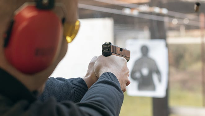 Aiming a pistol in a shooting range.