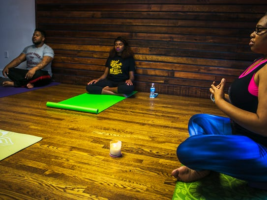 """Kyrus Jones (left) and Erica Perry listen to the guidance provided by yoga instructor Jackie Oh!, with Sapphire Yoga Sanctuary, during the """"Black Folks and Chill -- Let's be real, how does it feel?"""" event at Memphis Slim House."""