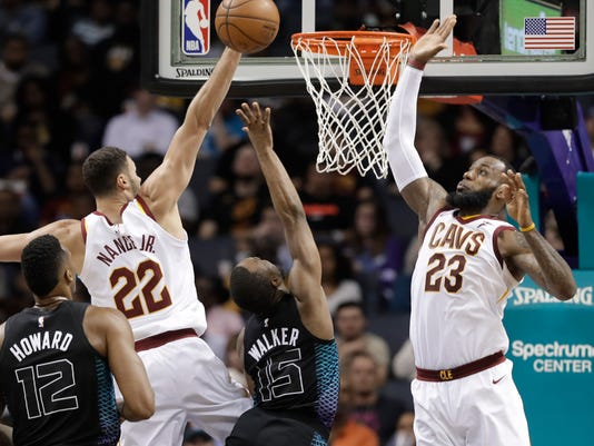 detailed pictures 622ce b6d98 Charlotte Hornets  Kemba Walker (15) shoots between Cleveland Cavaliers  LeBron  James (