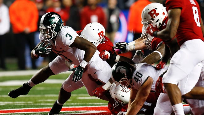 LJ Scott (3) of the Michigan State Spartans tries to break free from the line against the Rutgers Scarlet Knights. MSU won 40-7 to finish the regular season 9-3.