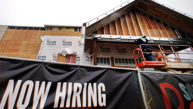 Aa now hiring sign hangs nearby as a builder works on a commercial property under construction in Peabody, Mass.