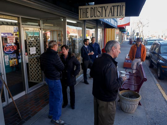 Community members stop and talk during a walking tour of downtown Farmington on Monday near the Dusty Attic on Main Street.
