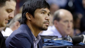 Boxer Manny Pacquiao watches the game between the Miami Heat and the Milwaukee Bucks on Tuesday night.