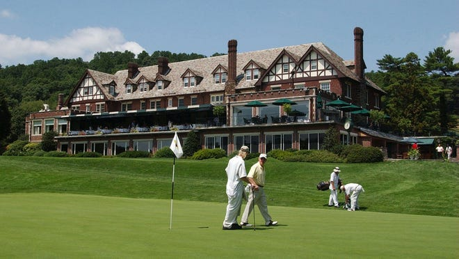 Golfers leave the 18th green in front of the clubhouse at Baltusrol Golf Club.