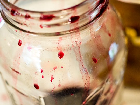 Grape juice is collected in a Ball jar for use later in cooking down Ren Weiner's wild Vermont grape jam.