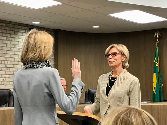 The newest, and youngest, city council member, Maria Taylor (left) takes the oath of office from Farmington Clerk Sue Halberstadt.