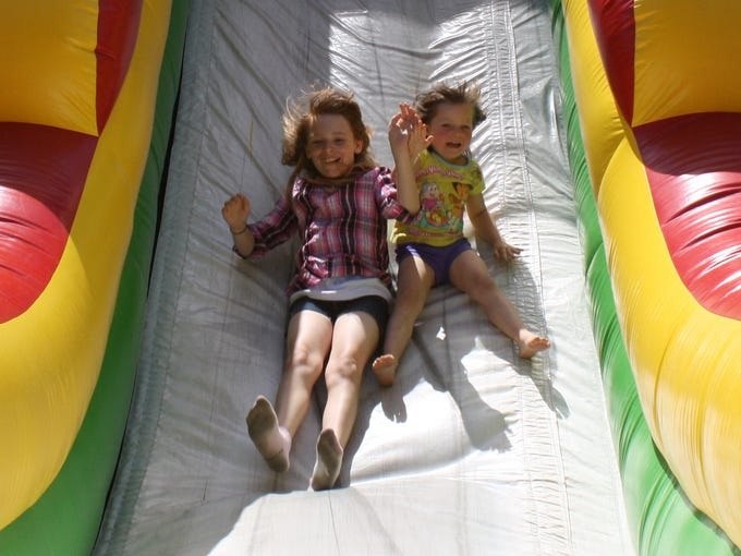 Soon-to-be sisters Amy Hesler, 10, and Kylei Wagoner, 4, brave the inflatable slide during the annual JEFF Fest in downtown Jeffersonville on Saturday.  (By Jenna Esarey, special to The Courier-Journal)  June 7, 2014.