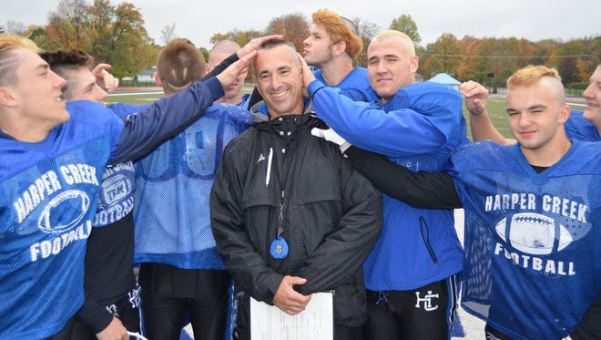 Harper Creek head coach Mike Seedorff shows off his mohawk after promising the team he would get a haircut if they went 9-0.