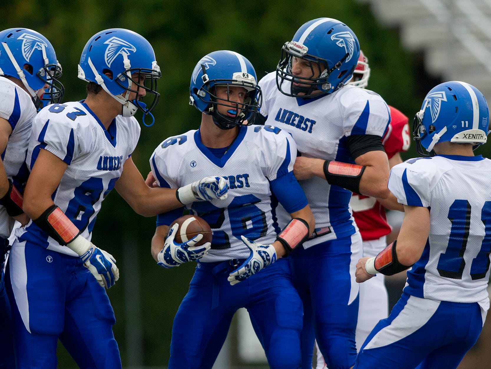 Amherst's Mitchell Glodowski, center, celebrates his touchdown in the first quarter with his teammates during the Central Wisconsin Conference football game against Pacelli at Goerke Field in Stevens Point on Friday, Sept. 18, 2015.