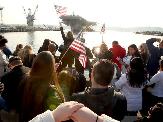 Flags are waved as the USS Nimitz pulls into the pier