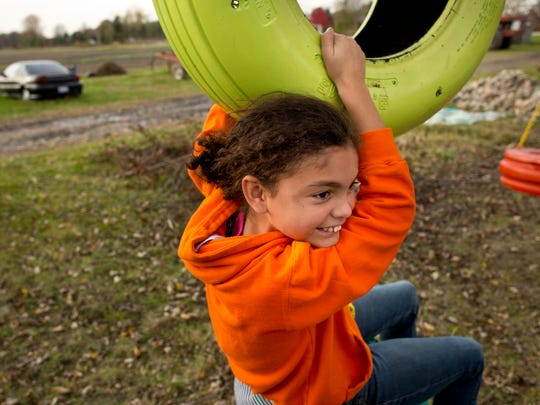Ceionna Simpson, 9, swings on a tire swing in the front yard at their home in Fort Gratiot.