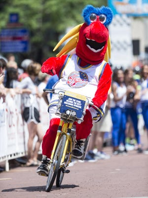 FILE -- Indiana Fever mascot Freddie Fever goofs off while taking his turn on the bike in the VIP Celebrity Relay Race. Cyclists of all levels converged on downtown Indianapolis, Saturday, July 8, 2017, to participate in The 8th annual Indy Criterium. Racing takes place on the 0.95 mile closed course that starts and finishes just north of Monument Circle. 100% of the event proceeds have benefited Freewheelin' Community Bikes, a local community bike shop and youth organization that serves kids in the Indianapolis community.