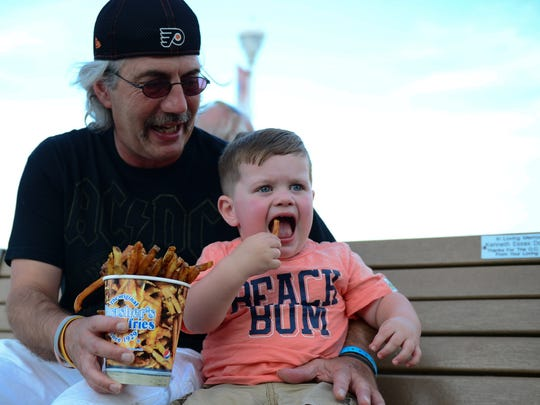 Geppi Altomare and his grandson Miles, 2, from Telford, Pa enjoy their Thrasher's french fries on the boardwalk on Wednesday, Aug. 31.
