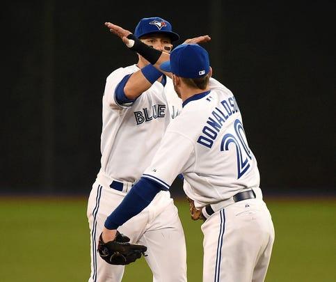Toronto Blue Jays third baseman Josh Donaldson (20) and shortstop Troy Tulowitzki (2) celebrate a 3-1 win over Minnesota Twins at Rogers Centre.