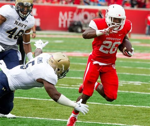 Houston's running back Tyreik Gray (26) avoids the tackle from Navy's cornerback Quincy Adams (5), scoring on the play during the first quarter of an NCAA college football game Friday in Houston.