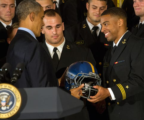 U.S. Naval Academy co-captain and college record-breaking quarterback Keenan Reynolds, right, presents President Obama with a team helmet during Commander in Chief's Trophy award ceremony at the White House on April 27, 2016, in Washington.