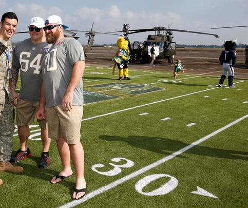 Buffalo Bills offensive guard Richie Incognito (64) and Tampa Bay Buccaneers guard Logan Mankins (70) pose for a selfie with a soldier at the NFL Pro Bowl football draft at Wheeler Army Airfield, Wednesday, Jan. 27, 2016, in Wahiawa, Hawaii.