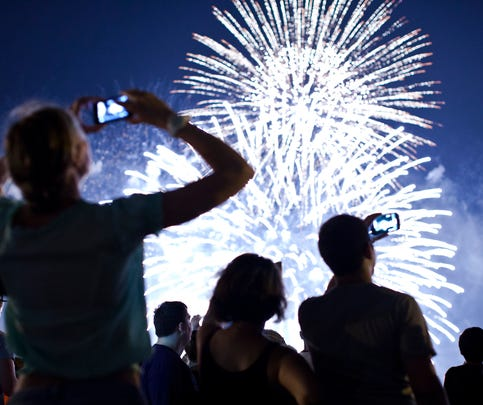 WEEHAWKEN, NJ - JULY 4: People watch fireworks light up the sky over New York City on July 4, 2013 in Weehawken, New Jersey. July 4th is a national holiday with the nation celebrating its 238th birthday.