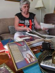 Ann Hollingsworth of Williamston looks through scrapbooks