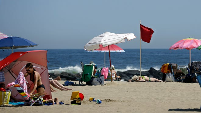 A red flag signaling beachgoers that no swimming is allowed is seen on the beach near the ocean Monday, Aug. 25, 2014, in Spring Lake, N.J. (AP Photo/Mel Evans)