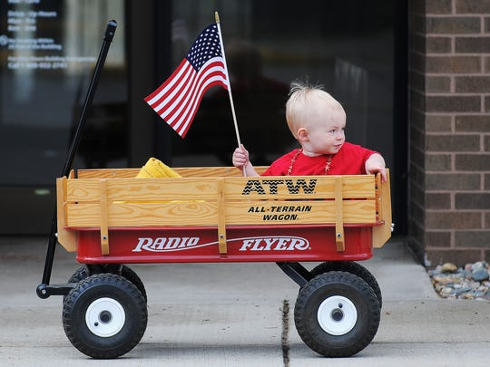 Peter Sorenson, 1, sits in his wagon waving an American Flag while waiting for the start of the Dell Rapids Memorial Day parade on Monday.