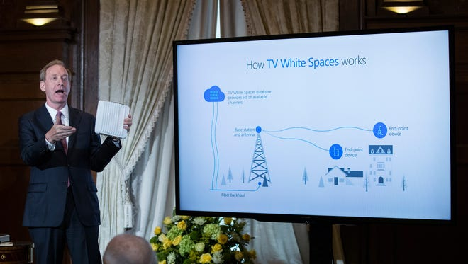 Brad Smith, President and Chief Legal Officer of Microsoft, holds up an ACRS2 device by ADAPTRUM used in TV White Space communications as he speaks at the Willard Hotel in Washington, Tuesday, July 11, 2017, about Microsoft's project to bring broadband internet access to rural parts of the United States.