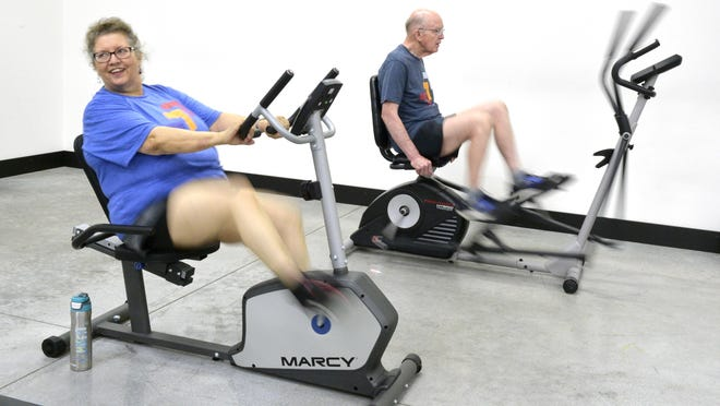 """FILE - Lynn Skeen (left) and John Trulock, who both have Parkinson's disease, pedal their stationary bikes as part of a ride against cancer at Day One Fitness in Beech Island. The two are part of a group of 21 """"virtual riders"""" raising money for the Paceline cycling charity event."""