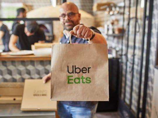 Man holding up an Uber Eats bag in restaurant