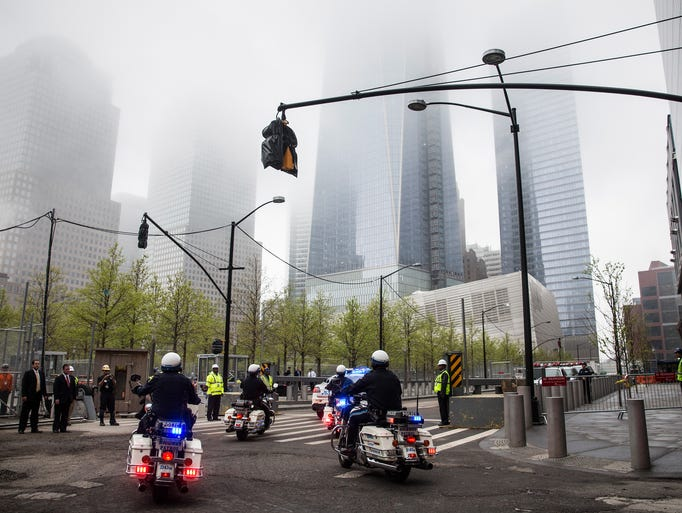 New York police officers on motorcycles escort emergency vehicles transporting the unidentified remains of victims of the Sept. 11, 2001, attacks onto the World Trade Center site, where they will be kept at the 9-11 Museum in New York City.