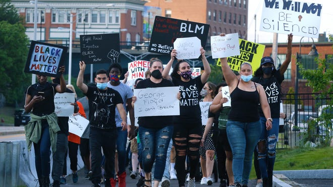 Protesters chant during a George Floyd-inspired march for racial justice in Woonsocket earlier this month.