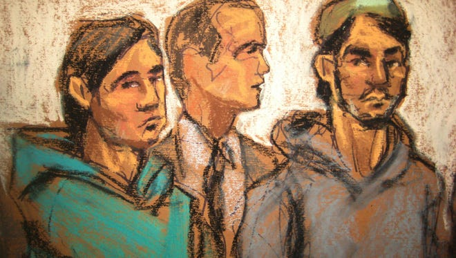 In this courtroom drawing, defendant Akhror Saidakmetov, left; an interpreter, center; and defendant Abdurasul Hasanovich Juraboev, appear at federal court in New York on terrorism charges, Wednesday, Feb. 25, 2015.