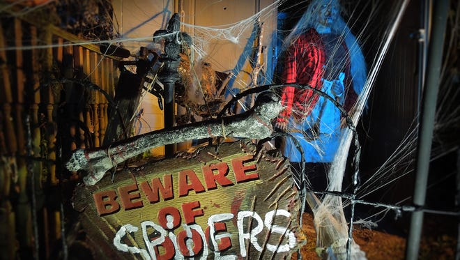Shawn and Lynne Mitchell's haunted yard comes to life at night, crawling with spiders.